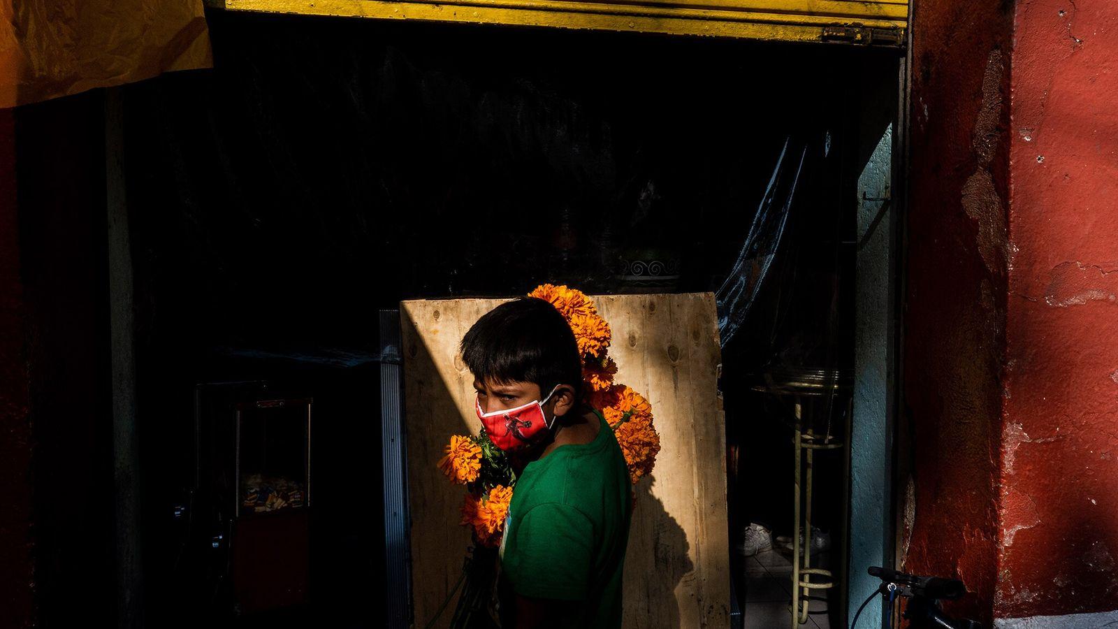 Un niño con un ramo de cempasúchil espera a su madre fuera de una pastelería mientras ...
