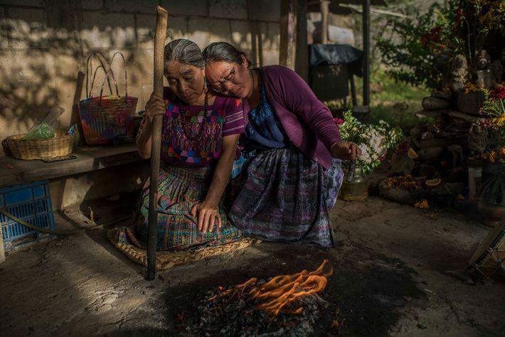 Maria Saturnina Us Álvarez (izquierda) y su hija, Rosario Tuyuc, en su hogar durante una ceremonia maya en honor a ...