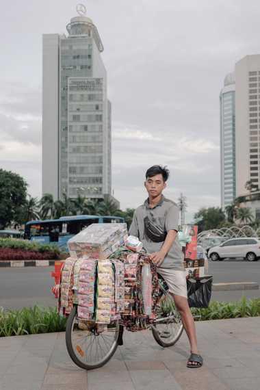 Fauzi, un trabajador informal, vende café instantáneo cerca del Hotel Indonesia Roundabout, una popular zona peatonal ...