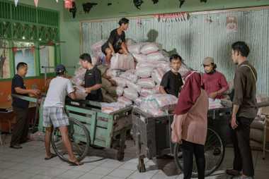 Los voluntarios de Foodbank of Indonesia descargan y almacenan 20 toneladas de sacos de arroz en un ...