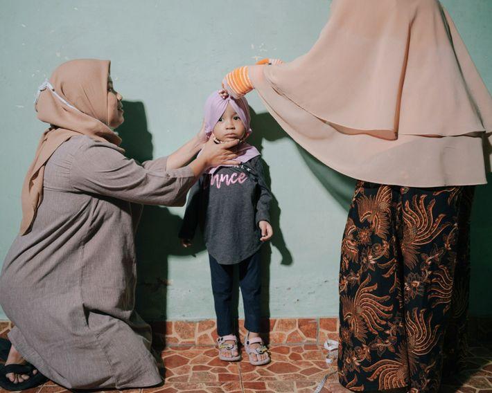 Roozmalinie (izquierda) sostiene a su hija Aquilla de 3 años (centro) mientras Kris Wati (derecha) la ...