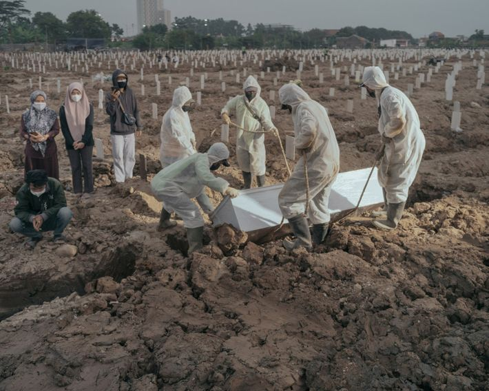Los trabajadores colocan a una víctima de la COVID-19 en una tumba del cementerio público de ...