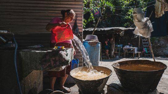 María Isabel, de 54 años de edad, usa una cubeta de agua para limpiar el maíz ...