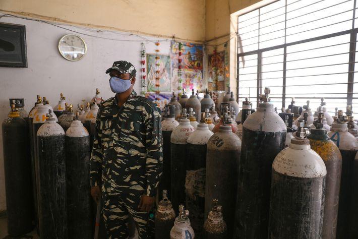 Un soldado paramilitar indio hace guardia en un centro de rellenado de oxígeno en Nueva Delhi ...
