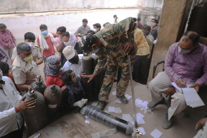 El personal paramilitar indio hace guardia mientras la gente recoge fichas para rellenar cilindros de oxígeno ...
