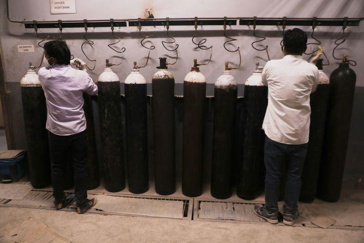 Los trabajadores del hospital de Venkateshwar en Dwarka, Nueva Delhi, conectan cilindros de oxígeno a la ...