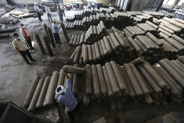 Los trabajadores mueven los cilindros recién fabricados para transportarlos a la fábrica Bharat Pumps and Compressor ...