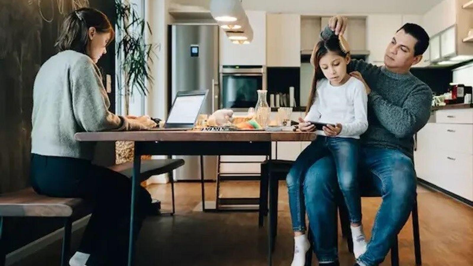 Imagen de una madre trabajando mientras el padre peina a su hija.
