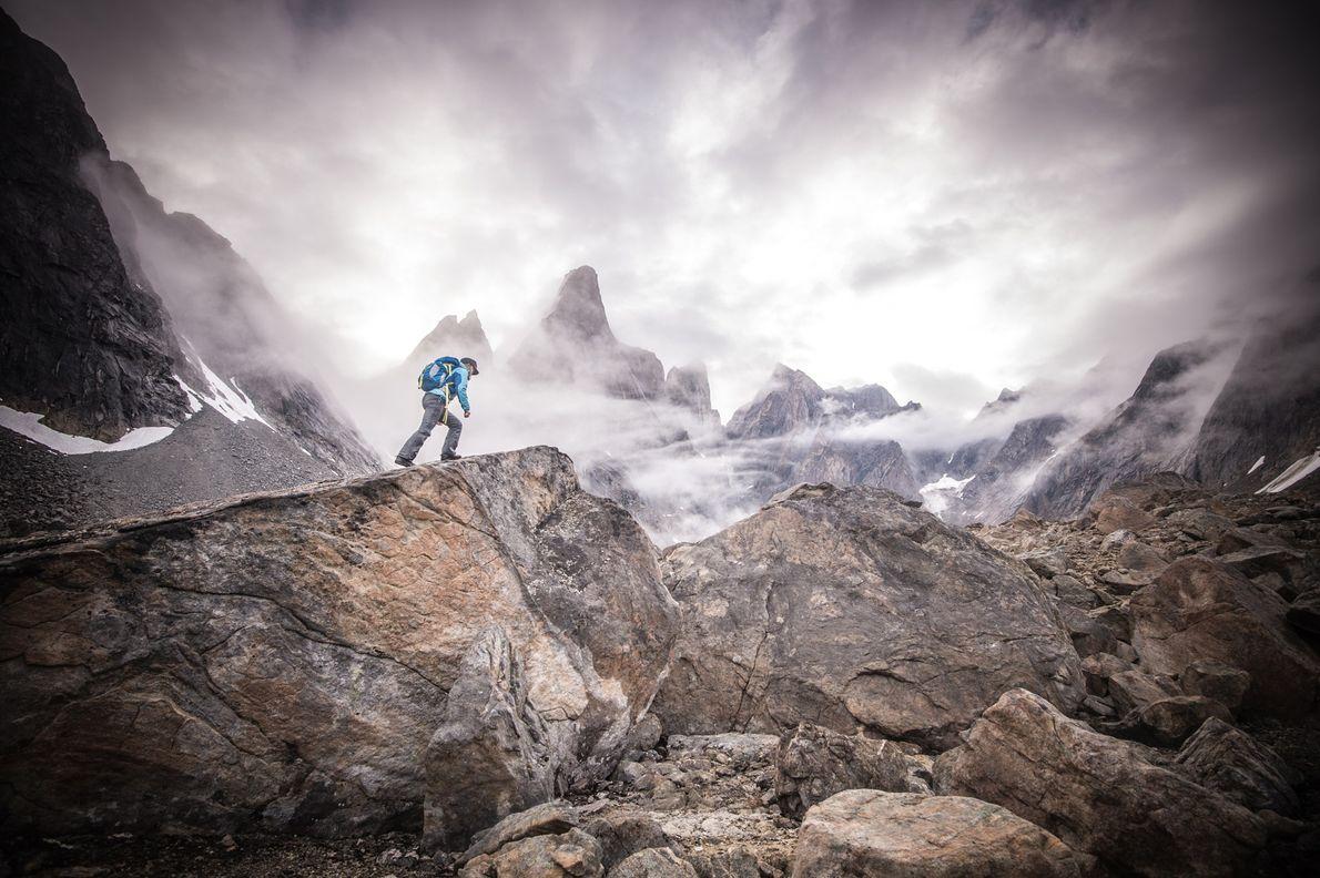 En el sureste de Groenlandia, un excursionista solitario escala el terreno rocoso. El este de Groenlandia ...