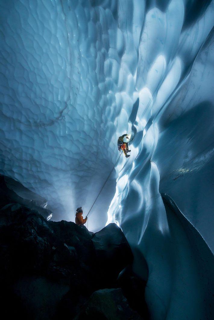 Un miembro del equipo desciende sujetado a una cuerda por una sección del cráter que lleva ...