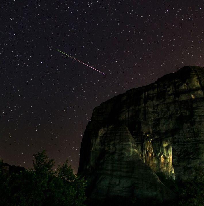 Un meteoro de las Perseidas atraviesa los acantilados de arenisca en el sitio del Patrimonio Mundial ...