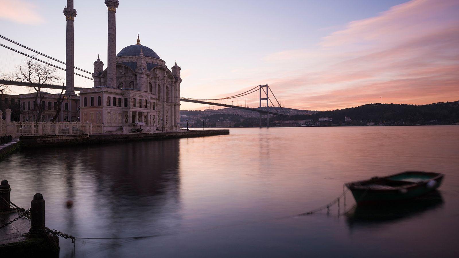 El amanecer arroja un brillo rosado en la mezquita Ortakoy en Estambul, Turquía. Las perforaciones en ...