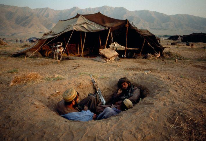 Dos combatientes afganos buscan cubrirse, con lo poco que tienen, durante el conflicto en 2001. Estados ...