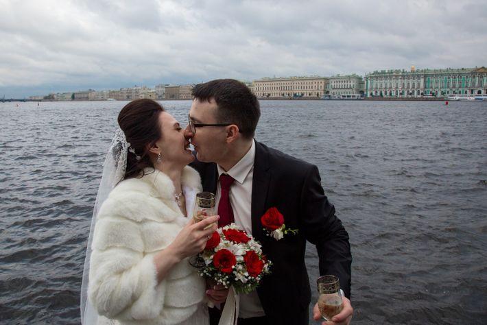 Una pareja de recién casados se saca fotos a orillas del Río Neva con el Museo ...