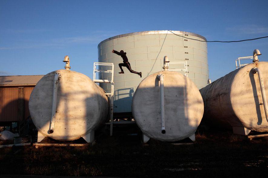 Los niños juegan sobre las antiguas instalaciones de tratamiento de agua de Newtok.