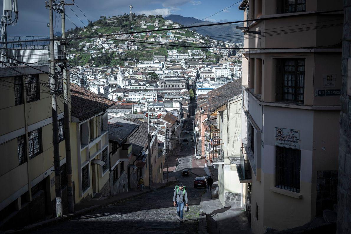 Un repartidor de delivery camina por las calles del centro de Quito, Ecuador. Todas las mañanas deja ...