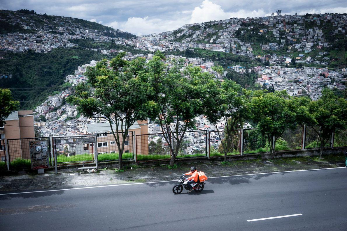 """Un repartidor de delivery en motocicleta pasando sobre la calle Quseras del Medio en Quito, Ecuador. """"Durante ..."""