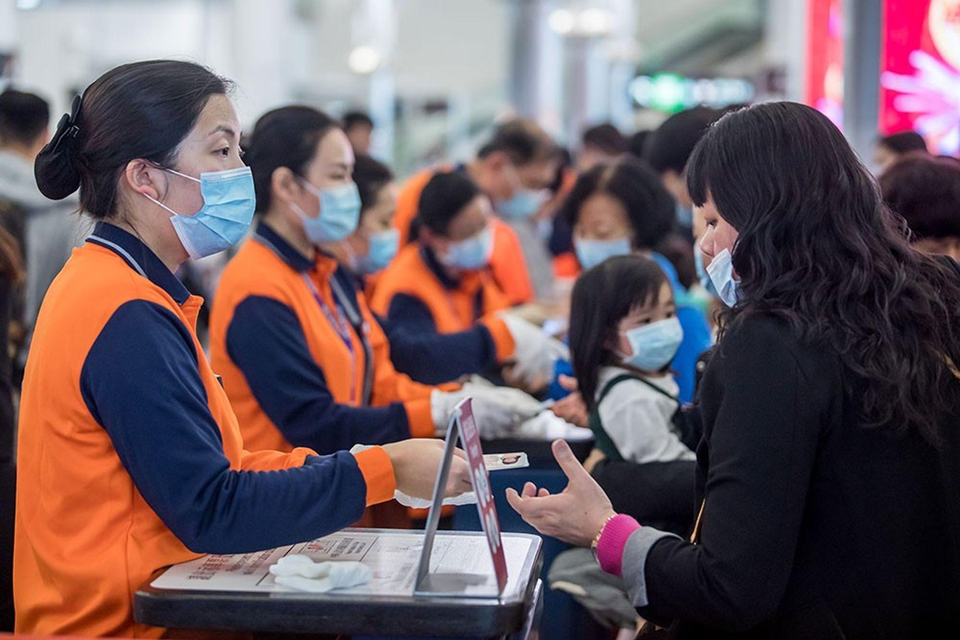 Los trabajadores ferroviarios de Hong Kong, con chalecos naranjas y máscaras faciales, verifican las identificaciones de ...