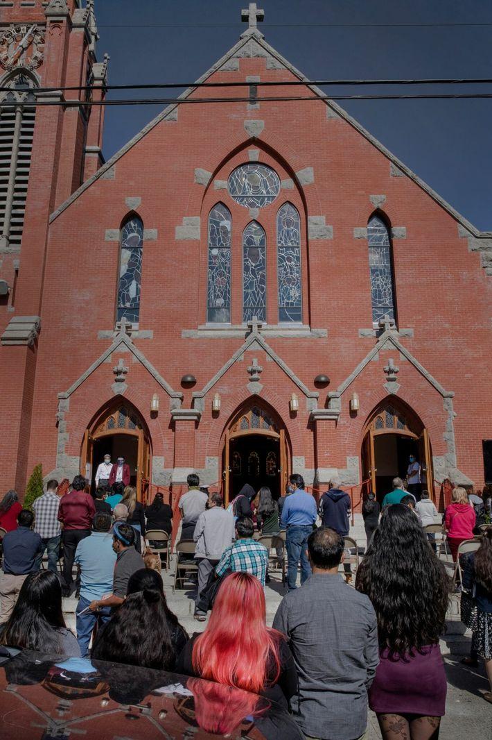 Los fieles rezan en un servicio de domingo en la iglesia católica Our Lady of Sorrows ...