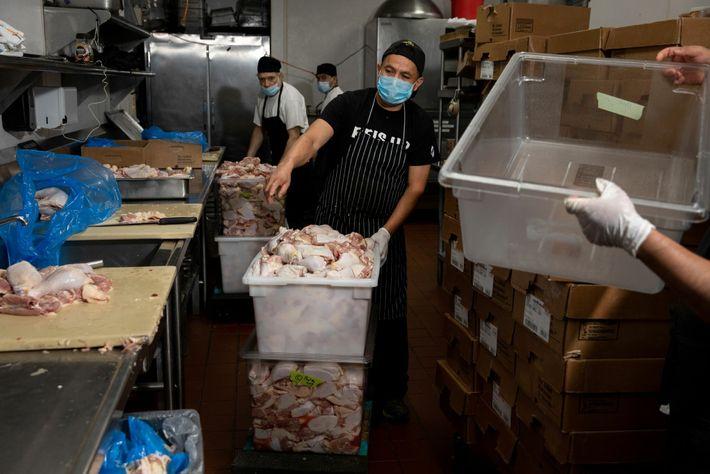 Los cocineros dan vuelta las cubetas de pollo crudo para cocinarlo en Test Kitchen de Migrant ...