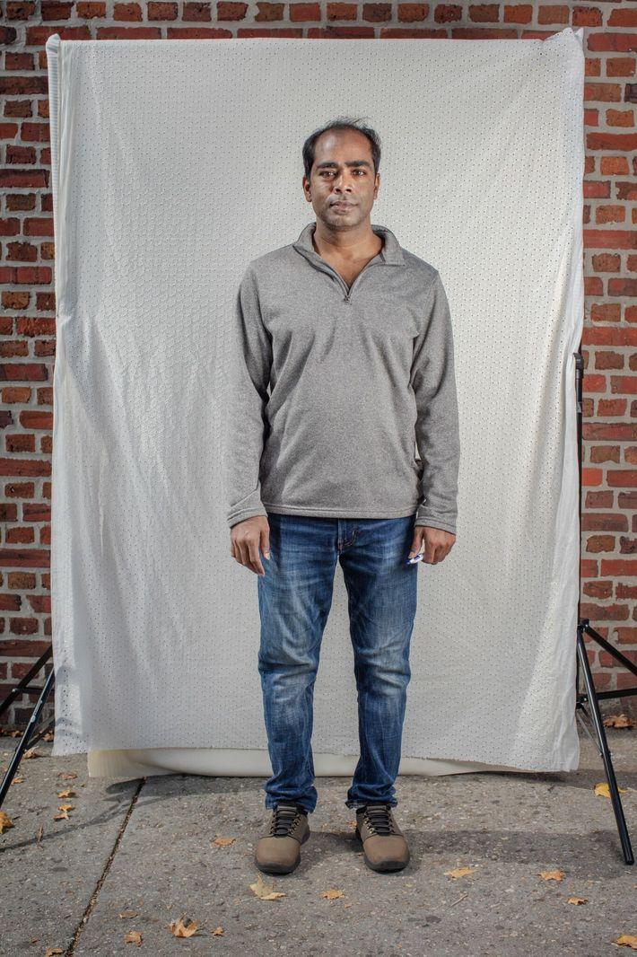 Muhammad Mostafa posa para el retrato mientras espera en fila en CENTI en Jackson Heights, Queens. ...