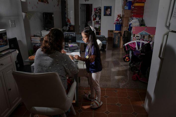 Ciria Santiago ayuda a su hija Katya con su clase de matemática en línea en su ...