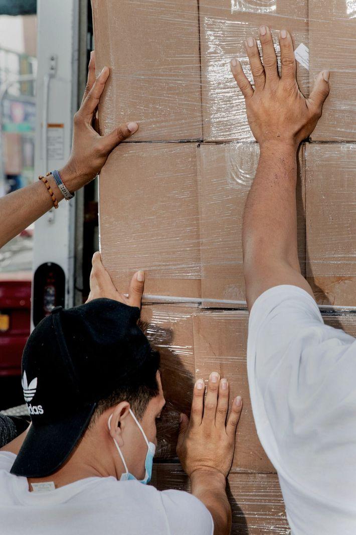 Un grupo de voluntarios en Latinos Unidos descarga un envío de leche y comida para ser ...