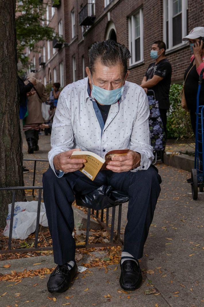 Luis Hernán Rea lee la Biblia mientras espera en una fila que se extiende por toda ...