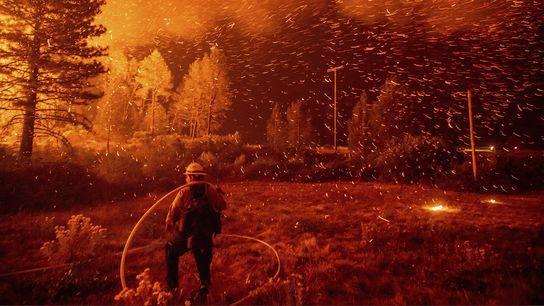 Las ascuas vuelan sobre un bombero que trabaja para contener el incendio de Delta, en el ...