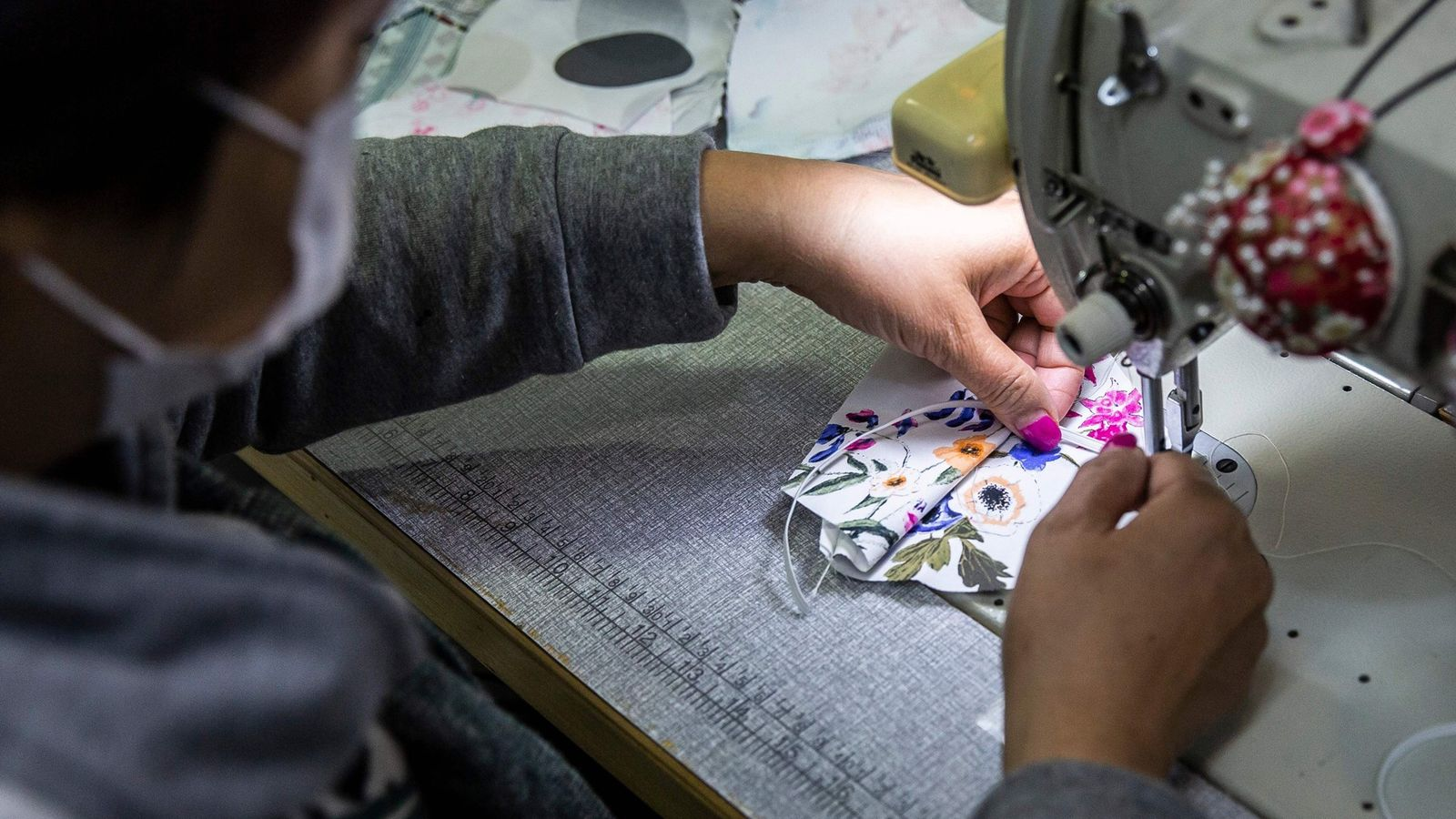 Tailor Elase Wong se encuentra haciendo mascarillas de material estampado en una tienda en Hong Kong ...