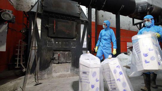Trabajadores en Kiev, Ucrania, desechan máscaras médicas y guantes usados quemándolos en un incinerador.