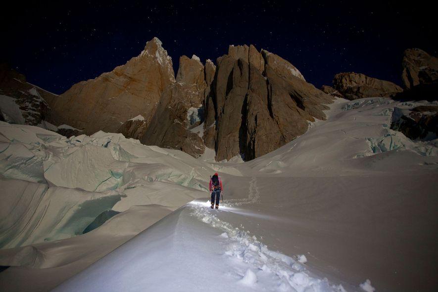 Un montañista ilumina una cresta nevada en el macizo de Torres en la Patagonia.