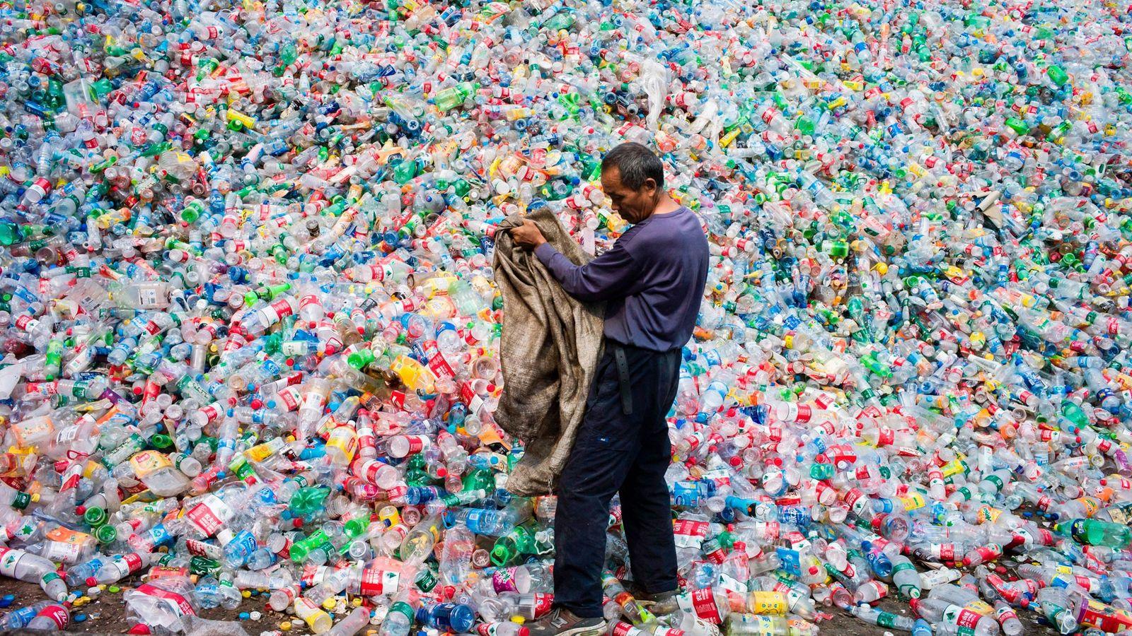 Un trabajador chino selecciona botellas de plástico en una operación de reciclaje en la aldea de ...