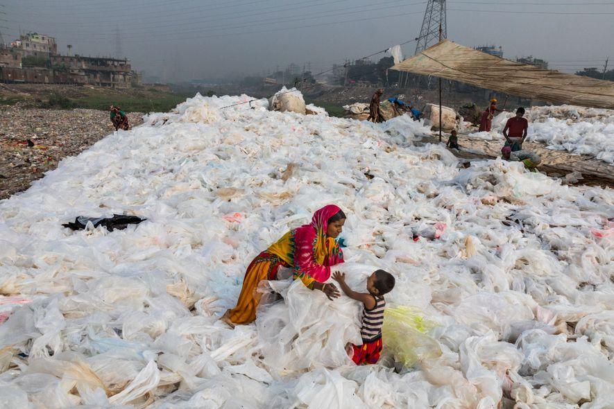 Junto a su hijo, Momo, Noorjahan extiende las sábanas de basura plástica que fue arrastrada a ...