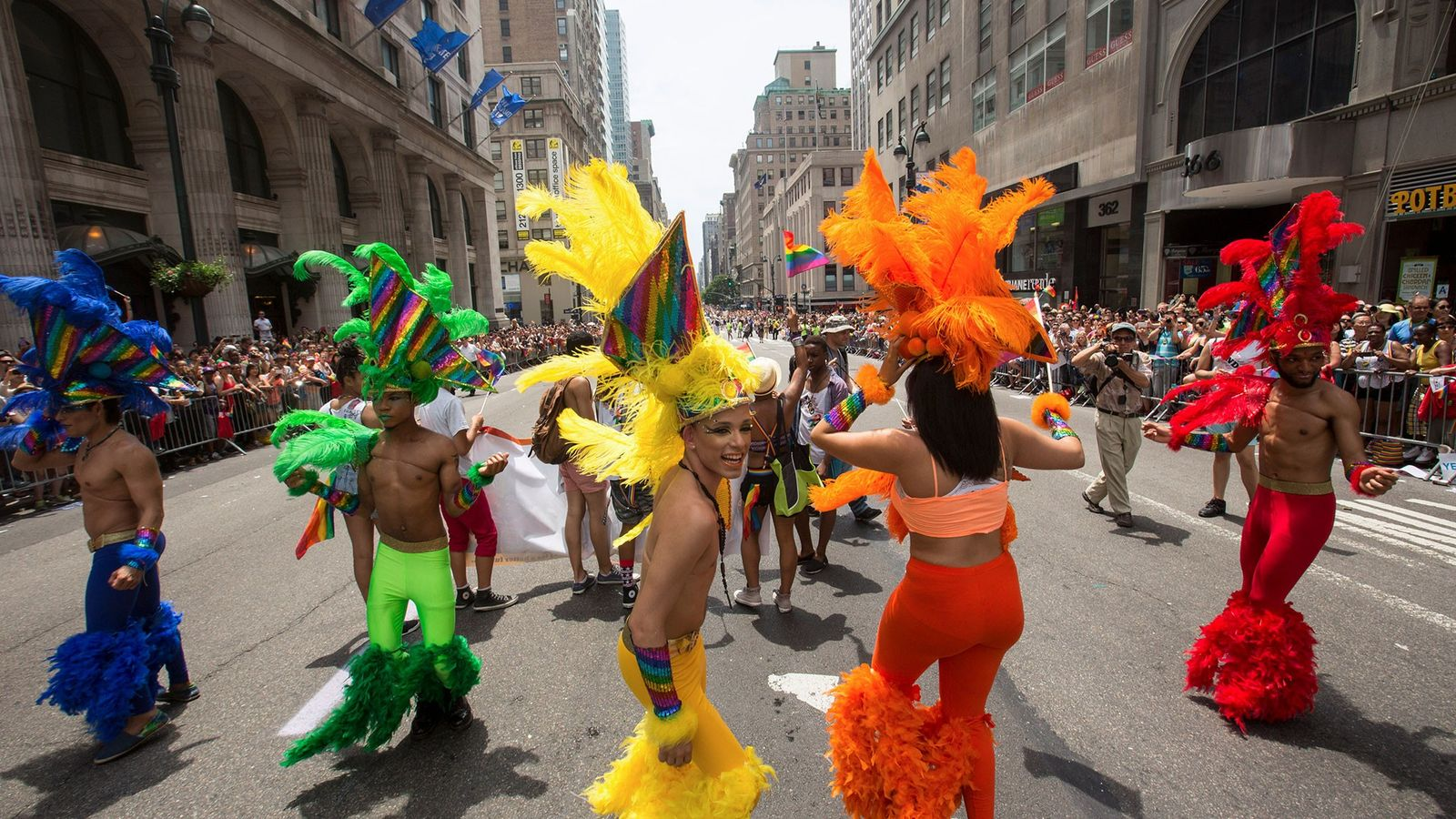 Bailarines desfilan vestidos con disfraces coloridos durante la manifestación del orgullo en Nueva York.