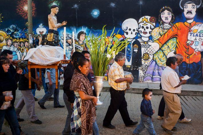 Los participantes caminan por una calle que tiene murales pintados durante el Día de los Muertos.