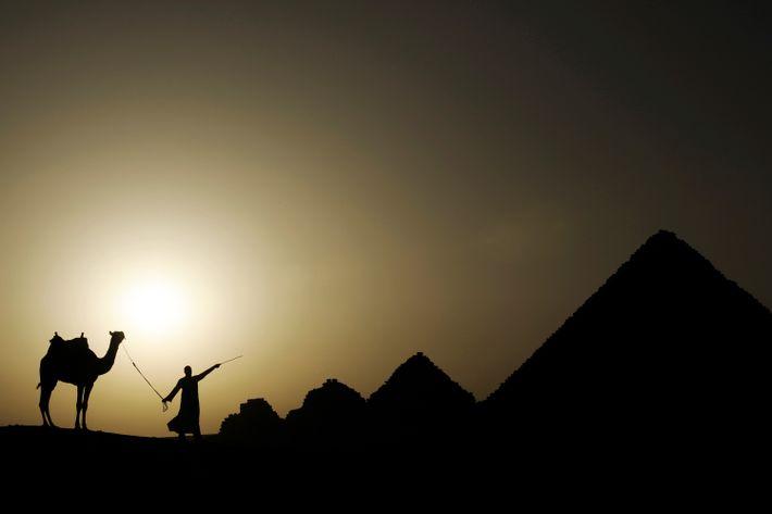 El sol poniéndose sobre la necrópolis de Guiza en las afueras del Cairo, Egipto.