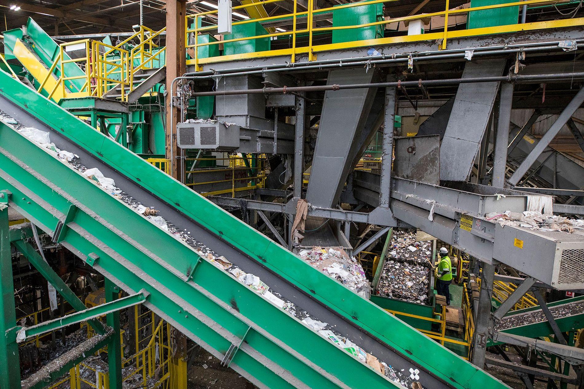 Los plásticos mezclados son transportados hacia un clasificador óptico en una planta de reciclaje. La industria está experimentando cambios rápidos, lo cual, a veces, confunde a los consumidores.