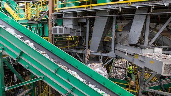 Los plásticos mezclados son transportados hacia un clasificador óptico en una planta de reciclaje. La industria ...