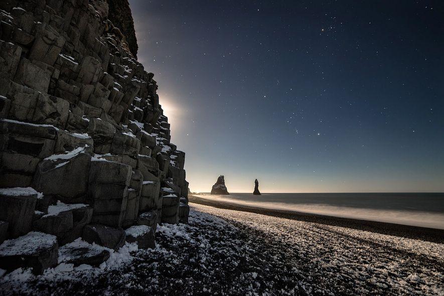 Se asoma la luna en Reynisfjara Beach, Islandia.