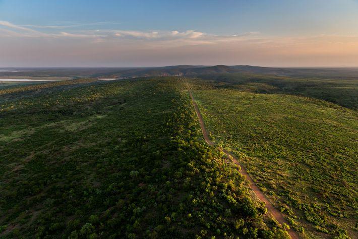 Una valla delimita la frontera entre el Parque Nacional Kruger (lado izquierdo) y Mozambique. Kruger es ...