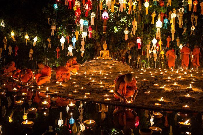 Los monjes encienden velas para la celebración de Loi Krathong en Wat Pahn Tao, un templo ...