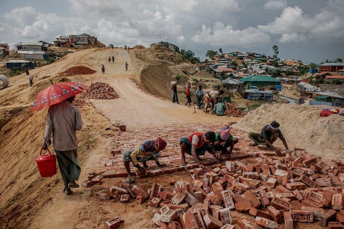 Los refugiados hacen un camino de ladrillos en el campamento de Balukhali, parte del sistema ampliado ...