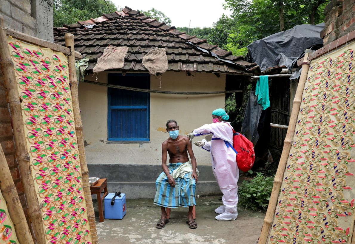 A villager receives a dose of COVISHIELD vaccine during a door-to-door vaccination and testing drive at ...