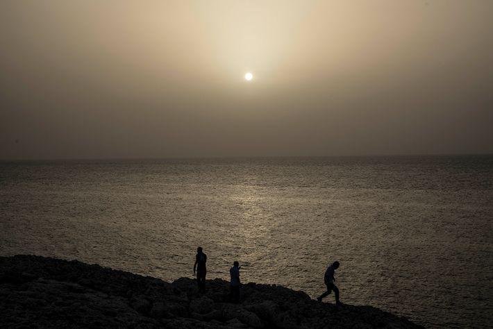 La gente mira el atardecer de colores extraños, teñido por la nube de polvo sahariano que ...