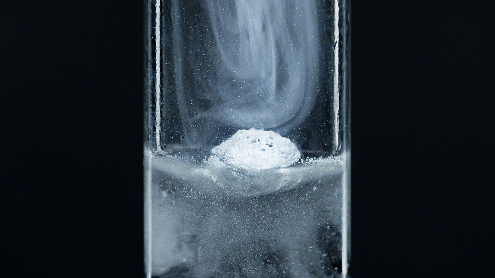 Cuando una pequeña partícula de potasio metálico se cae en un tubo de ensayo de agua, ...