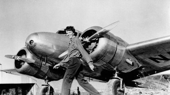 Amelia Earhart camina frente a su Lockheed Electra, el avión en el que desapareció en julio ...