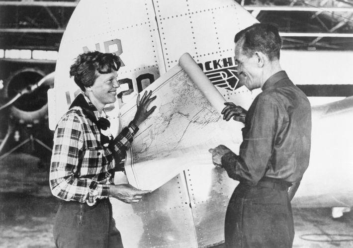 Earhart y el navegador Fred Noonan consultan un mapa del Pacífico que muestra la ruta planificada ...