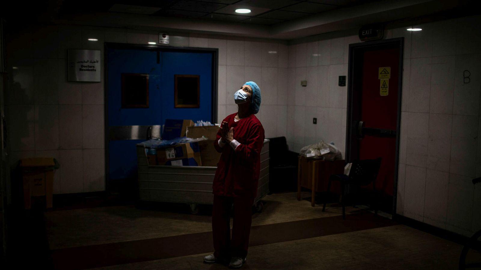 Una enfermera reza dentro de los pasillos de la Unidad de Cuidados Intensivos del Hospital Universitario ...