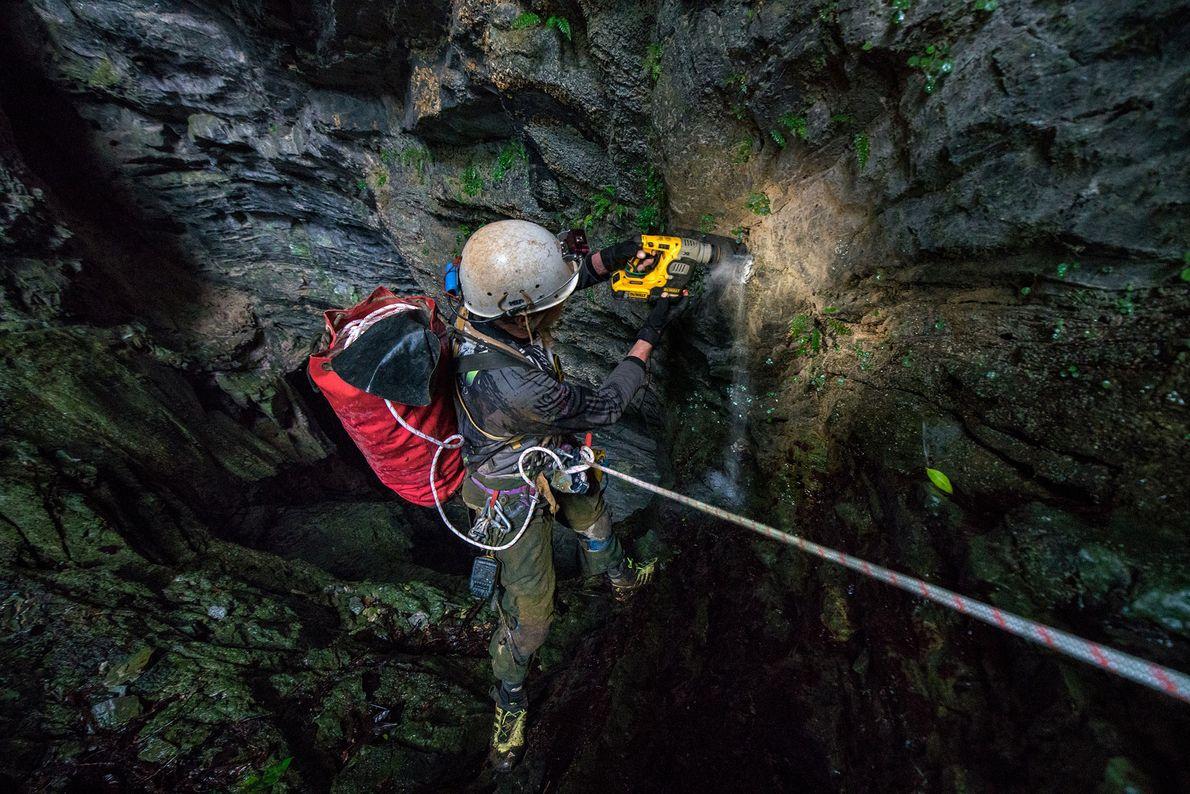 Chris Lloyd, un geólogo, perfora un hueco en una pared de piedra caliza para establecer una ...